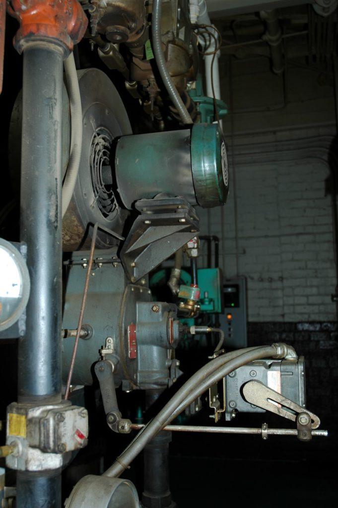 green and gray mechanical machine beside wall